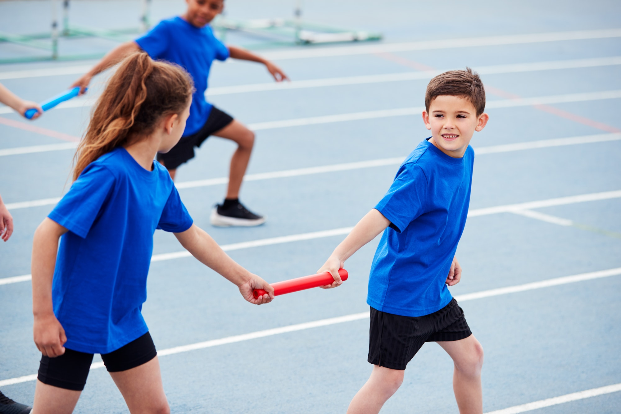 Children In Athletics Team Competing In Relay Race On Sports Day